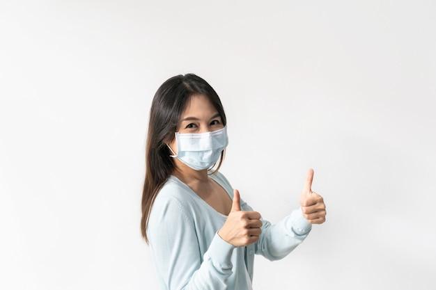 Portret kobiety noszącej maskę chirurgiczną kciuk w górę pozowanie i uśmiechanie się do kamery na białym tle