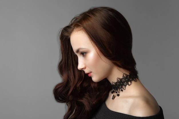 Portret kobiety o ciemnych włosach na szarej ścianie