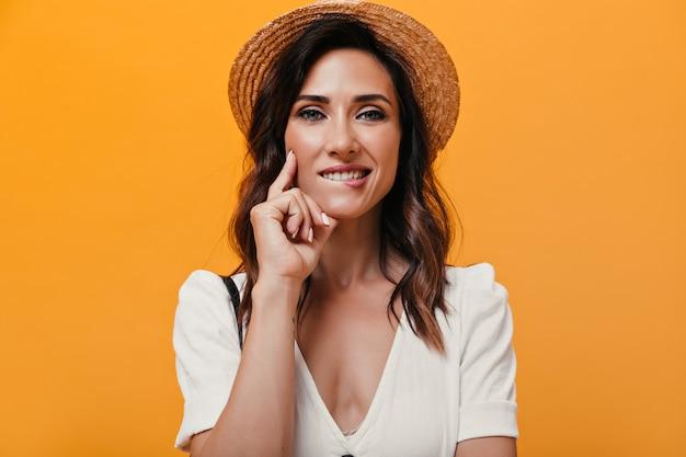 Portret kobiety o niebieskich oczach w słomkowym kapeluszu, który gryzie wargę. zdjęcie uroczej kobiety w słomkowym kapeluszu w białej sukni, patrząc na kamery.