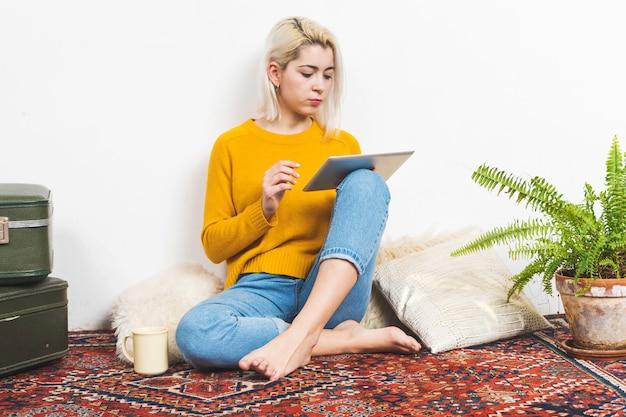 Portret kobiety obsiadanie na podłoga żywy pokój używać cyfrową pastylkę