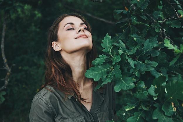 Portret kobiety oczy zamknięte, ciesząc się przyrodą zielonych liści latem przycięty widok