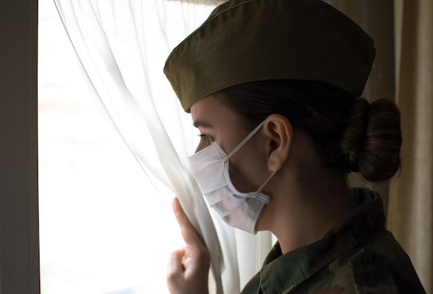 Portret kobiety oficer armii w mundurze i masce chirurgicznej. patrząc przez okno