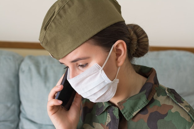 Portret kobiety oficer armii w mundurze i masce chirurgicznej. rozmowa z telefonem komórkowym