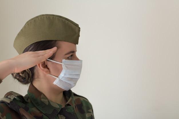 Portret kobiety oficer armii w mundurze i masce chirurgicznej. salutowanie wojskowe