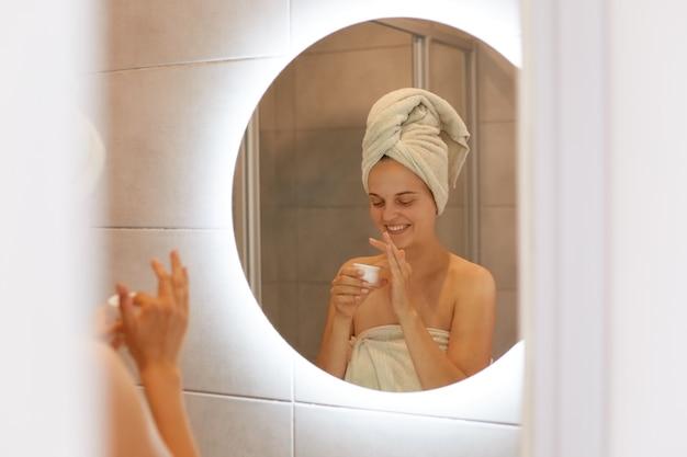 Portret kobiety owiniętej w biały ręcznik pozuje w łazience przed lustrem otwarty krem do nakładania na twarz, wyrażający szczęście, pielęgnację skóry i kosmetologię.