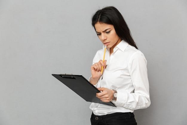 Portret kobiety pakietu office z długimi ciemnymi włosami na sobie białą koszulę, trzymając schowek z papierami i badanie dokumentów, odizolowane na szarym tle