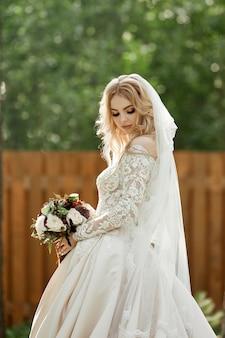 Portret kobiety panny młodej w sukni ślubnej z bukietem kwiatów w dłoniach