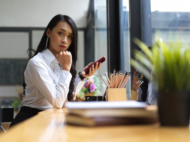 Portret kobiety patrząc w kamerę podczas korzystania ze smartfona na przenośnym obszarze roboczym w kawiarni