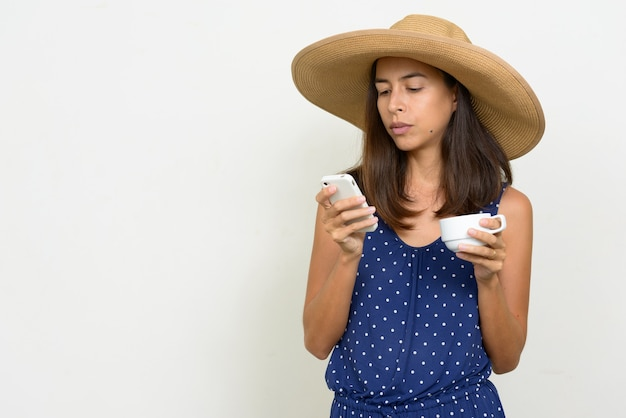 Portret kobiety piękne wieloetniczne turystyczne za pomocą telefonu trzymając filiżankę kawy