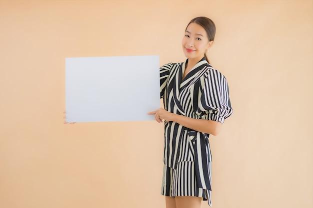 Portret kobiety pięknego młodego azjatykciego przedstawienia billboardu pusty biały papier