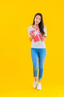 Portret kobiety pięknego młodego azjatykciego przedstawienia prezenta czerwony pudełko