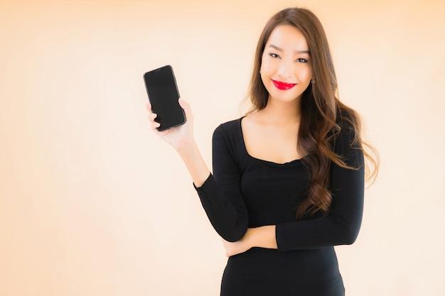 Portret kobiety pięknego młodego azjatykciego uśmiechu szczęśliwego use mądrze telefon komórkowy