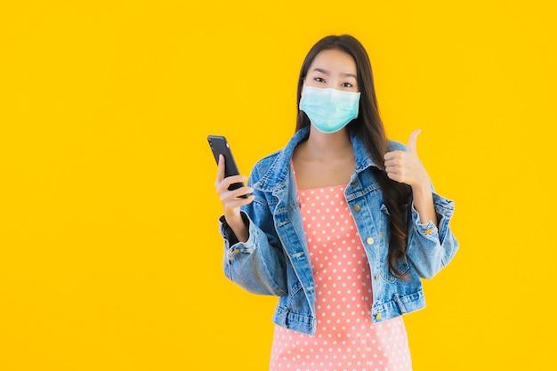 Portret kobiety pięknej młodej azjatykciej odzieży maski use smartphone