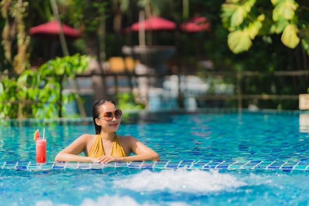 Portret kobiety piękny młody azjatykci czas wolny uśmiech z arbuza sokiem wokoło pływackiego basenu w hotelowym kurorcie