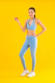 Portret kobiety piękny młody azjatykci odzieży sportwear przygotowywający dla ćwiczenia na kolorze żółtym