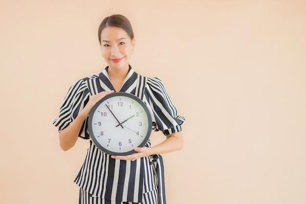 Portret kobiety piękny młody azjatykci przedstawienie zegar lub alarm