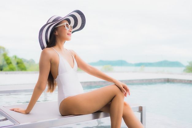 Portret kobiety piękny młody azjatykci uśmiech relaksuje i czas wolny wokoło plenerowego pływackiego basenu