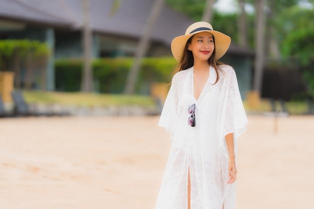 Portret kobiety piękny młody azjatykci uśmiech szczęśliwy relaksuje na plażowym dennym oceanie