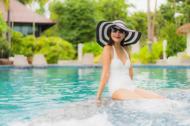 Portret kobiety piękny młody azjatykci uśmiech szczęśliwy relaksuje wokoło pływackiego basenu w hotelowym kurorcie