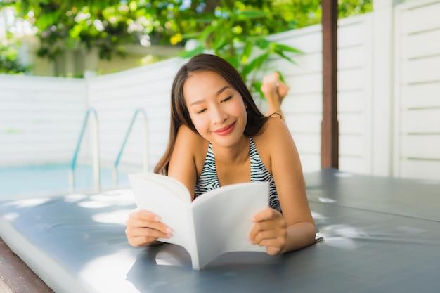 Portret kobiety piękny młody azjatykci uśmiech szczęśliwy relaksuje z czytelniczą książką wokoło pływackiego basenu