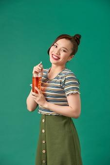 Portret kobiety pije sok pomarańczowy. sok pomarańczowy w szkle