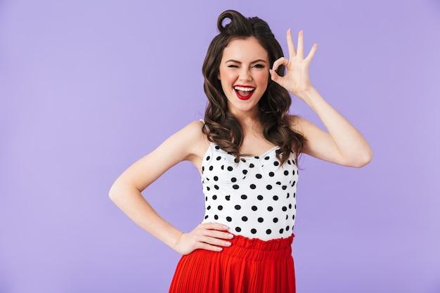 Portret kobiety pin-up glamour w sukienka vintage w kropki uśmiechający się i flirtujący do kamery na białym tle nad fioletową ścianą