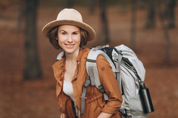 Portret kobiety podróżnik patrzeje zadziwiającego las z plecakiem, podróżuje pojęcie