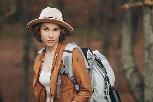 Portret kobiety podróżnik patrzeje zadziwiającego las z plecakiem
