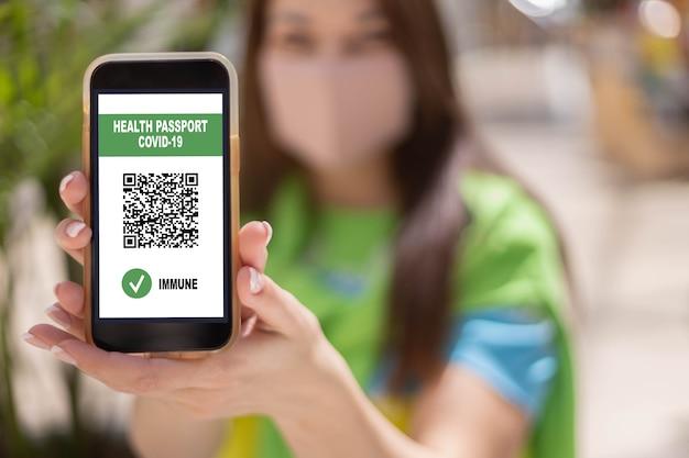 Portret kobiety podróżującej w masce na twarz z cyfrowym paszportem zdrowotnym aplikacji covid kod qr na smartfonie