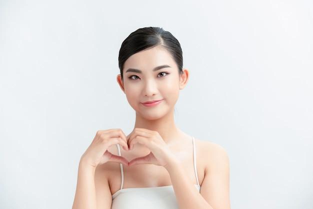 Portret kobiety pokazujący znak postaci serca z rękami w pobliżu klatki piersiowej na białym tle