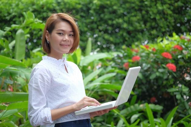 Portret kobiety pozycja trzyma laptopu komputer osobistego. uśmiechnięta kobieta przy zielony plenerowym z kopii przestrzenią