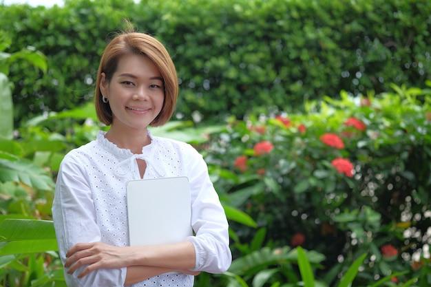 Portret kobiety pozycja trzyma pastylka komputer osobistego. uśmiechnięta kobieta przy zielony plenerowym z kopii przestrzenią