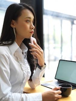 Portret kobiety pracownik biurowy zrelaksowany siedzi przy stole roboczym z filiżanką kawy i makiety tabletki