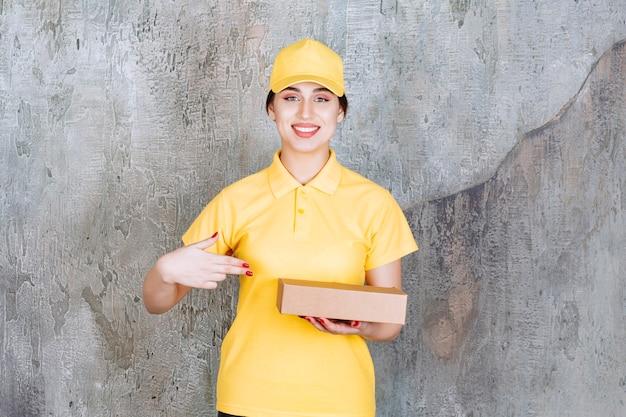 Portret kobiety pracownika dostawy trzymającej karton