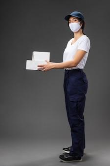 Portret kobiety pracuje dla firmy kurierskiej na sobie maskę