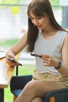 Portret kobiety przelewa pieniądze do wydania na zakupy online za pomocą smartfona i trzyma kartę kredytową