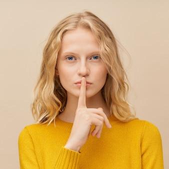 Portret kobiety przykładającej palec do ust, proszę nie hałasować, milczeć, milczeć