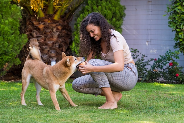 Portret kobiety przytulenie i całowanie jej pies w ogródzie
