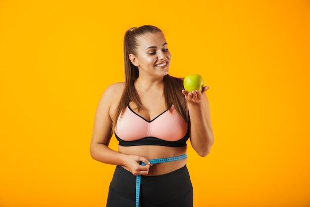 Portret kobiety pulchne fitness w stanik sportowy pomiaru jej talii miernikiem i trzymając jabłko, odizolowane na żółtym tle