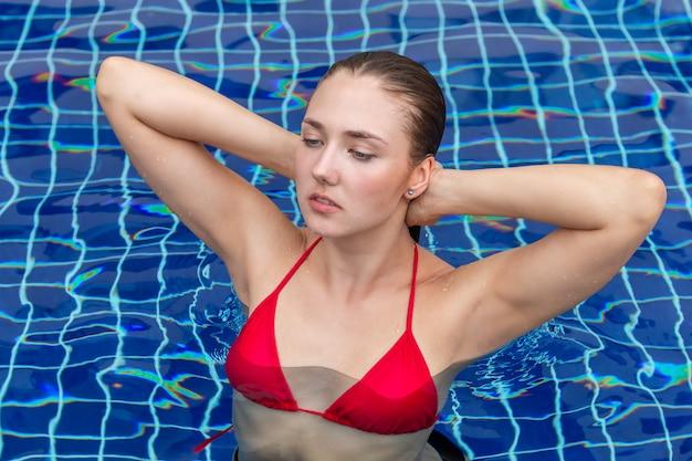 Portret kobiety rasy białej mody stojącej w basenie.