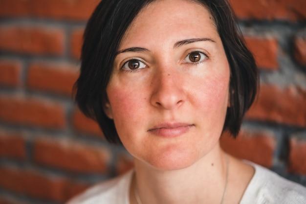 Portret kobiety rasy białej o zdrowych różowych policzkach i krótkich brązowych włosach