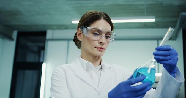 Portret kobiety rasy białej w okularach i białej szacie robi analizę niebieskiego płynu w probówce podczas badań medycznych lub farmaceutycznych oraz w laboratorium.