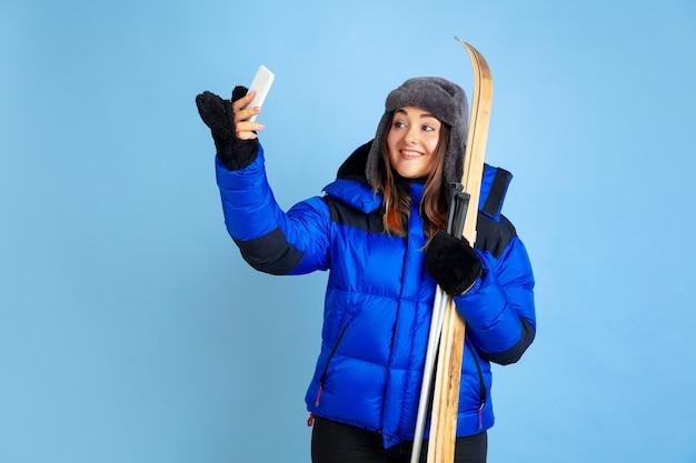 Portret kobiety rasy kaukaskiej na białym tle na niebieskim tle studio, motyw zimowy