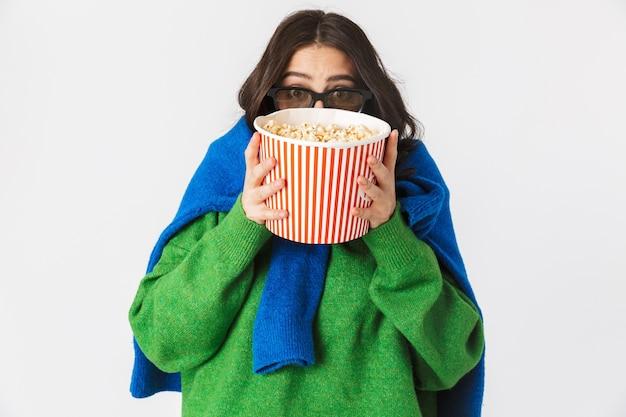 Portret kobiety rasy kaukaskiej w ubranie ubrane w okulary 3d jedzenie popcornu z wiadra, stojąc na białym tle