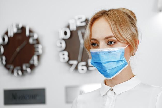 Portret kobiety recepcjonistka na sobie maskę medyczną