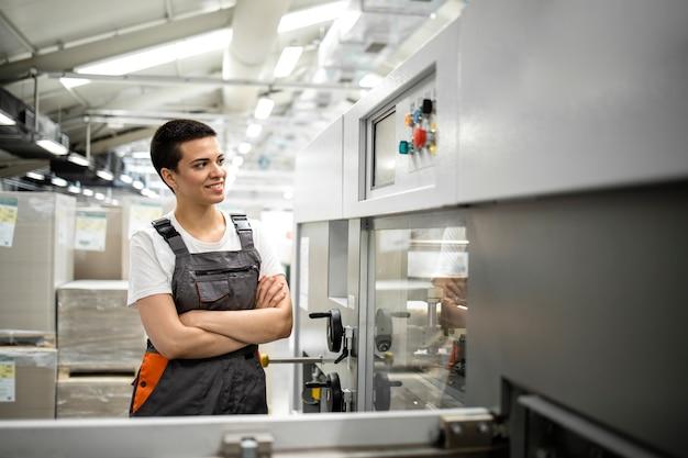 Portret kobiety robotnicy przemysłowej stojącej w fabryce przy produkcji maszyny