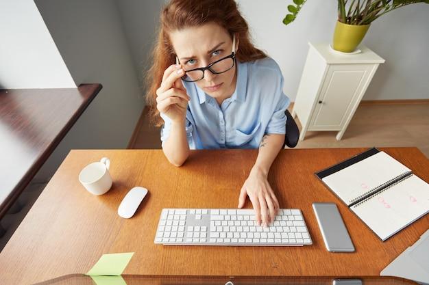 Portret kobiety rude w niebieskiej koszuli siedzi przy biurku przed komputerem