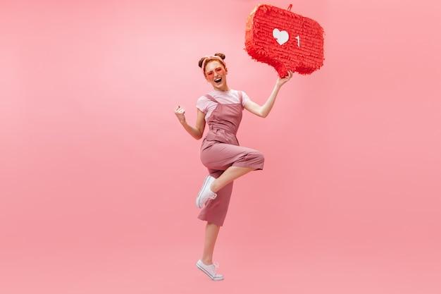 Portret kobiety rude w różowe okulary i kombinezon, raduje się ze zwycięstwa i skacze na na białym tle.