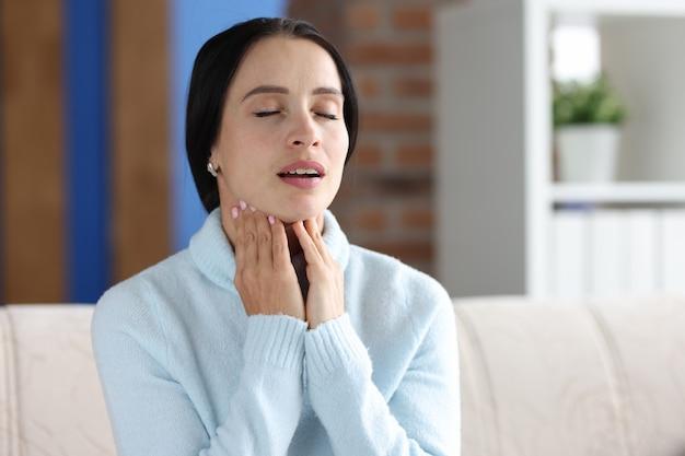 Portret kobiety siedzącej z zamkniętymi oczami i bólem gardła na kanapie. bolesne objawy w poczęciu gardła
