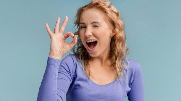 Portret kobiety, śmiejąc się i pokazując znak ok